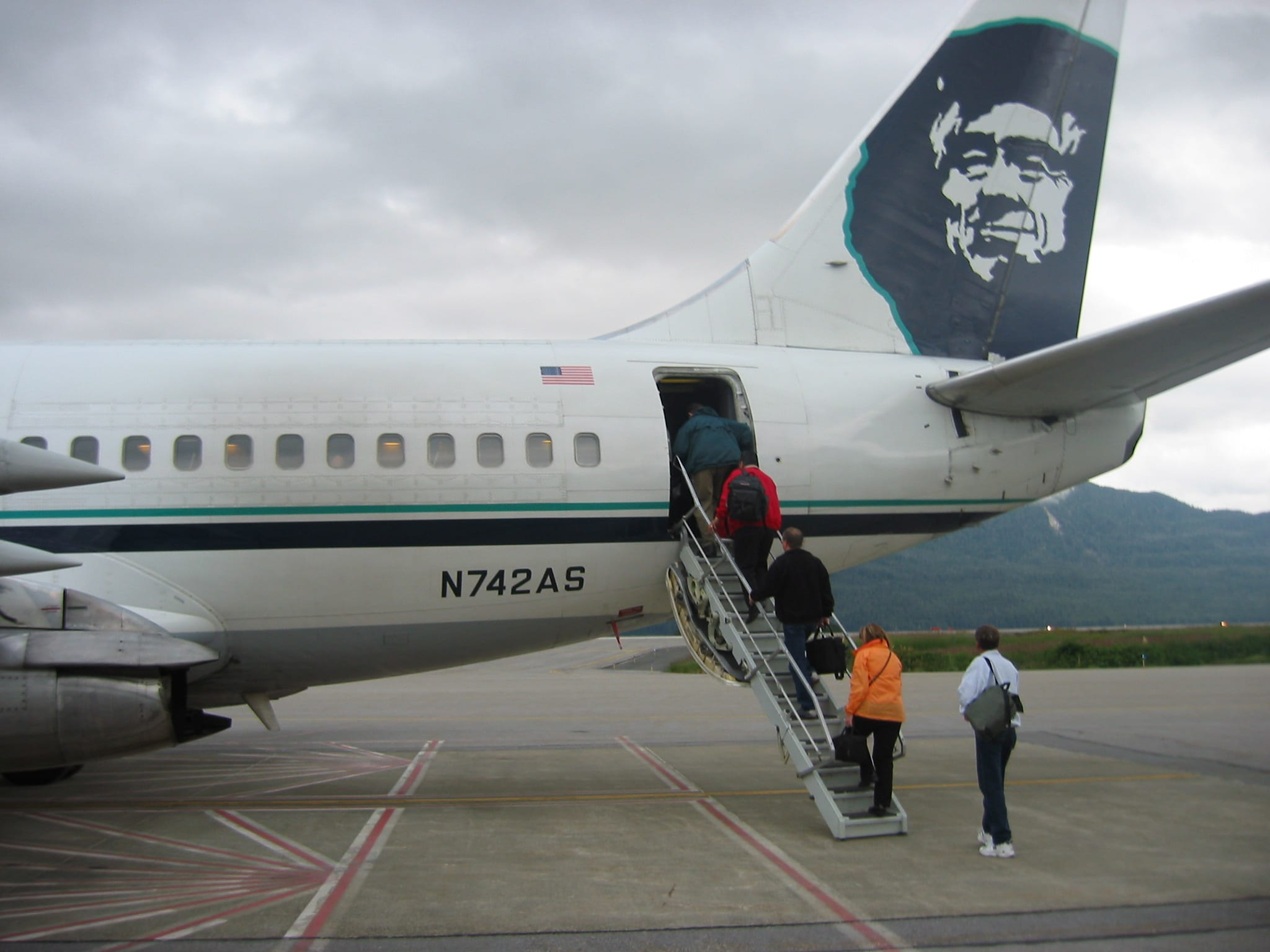 Passengers Board An Alaska Airlines Combi Plane By Stairs.