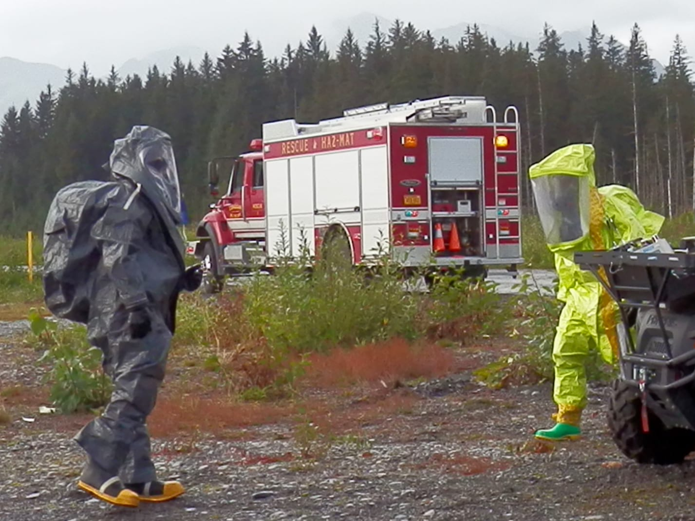 Cordova Volunteer Fire Department's Dustin Solberg, right, noted in the After Action Report on that emergency preparedness exercise that he was surprised how many people it took to support him in the decontamination hazmat suit as he searched for simulated cyanide victims. Photo by Mike Hicks/For The Cordova Times