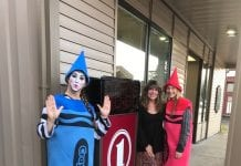 FNBA Branch Manager Cully Wooden and costumed Nicole Pallas look on as Mime Stacie Chappell expresses her Halloween delight at a new Main Street time and temperature clock. Photo by Dick Shellhorn/The Cordova Times
