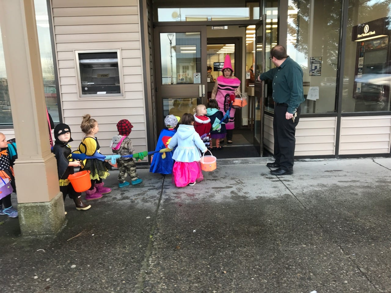 FNBA Operations Assistant Bryan Mills holds the door open as Children's Pallas trick-or-treaters, guided by Loreene Pallas, head in to begin their Main Street Halloween visits. Photo by Dick Shellhorn/The Cordova Times