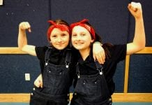 Third-grade Rosie the Riveter twins Isabella and Victoria Nothstine flex their muscles and smiles following the program's conclusion. Photo by Nicole Nothstine/For The Cordova Times
