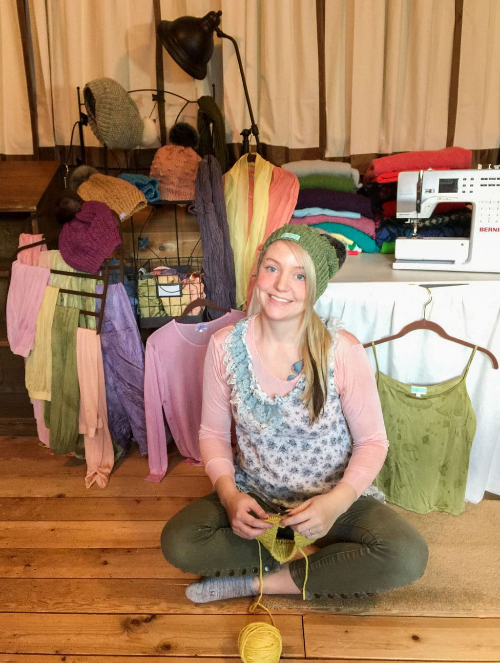 Amber Wasson, owner of Rainbow Forest, sits amid an array of her handmade, naturally dyed gift items. Wasson is wearing a hand-dyed silk undershirt dyed with cochineal bugs, and a hand knit beanie designed and made by Wasson. The yarn used to make the beanie was dyed using pincushion flowers. Photo courtesy Rainbow Forest/For The Cordova Times