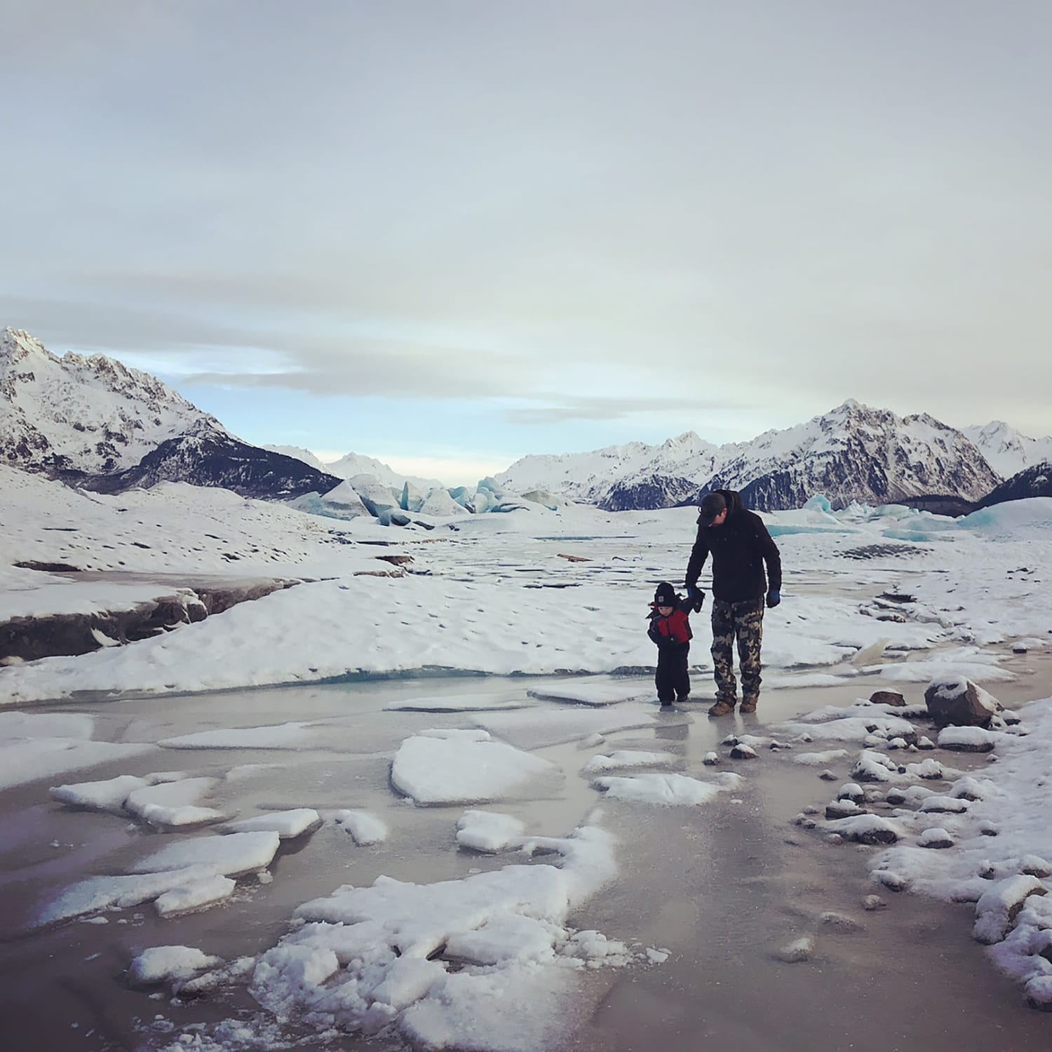 Father and son explore Sheridan Glacier together for the first time. Jared Kennedy, 39, and son Maverick, 3, both of Cordova walk along the frozen lake at Sheridan Glacier on Christmas Eve. The weather was calm, no wind, and not too cold; perfect for exploring. The elder Kennedy has landed on the ice with his Super Cub, but never hiked the glacier trail to walk on it. It was a memorable first for both. Photo by Vivian Kennedy/The Cordova Times
