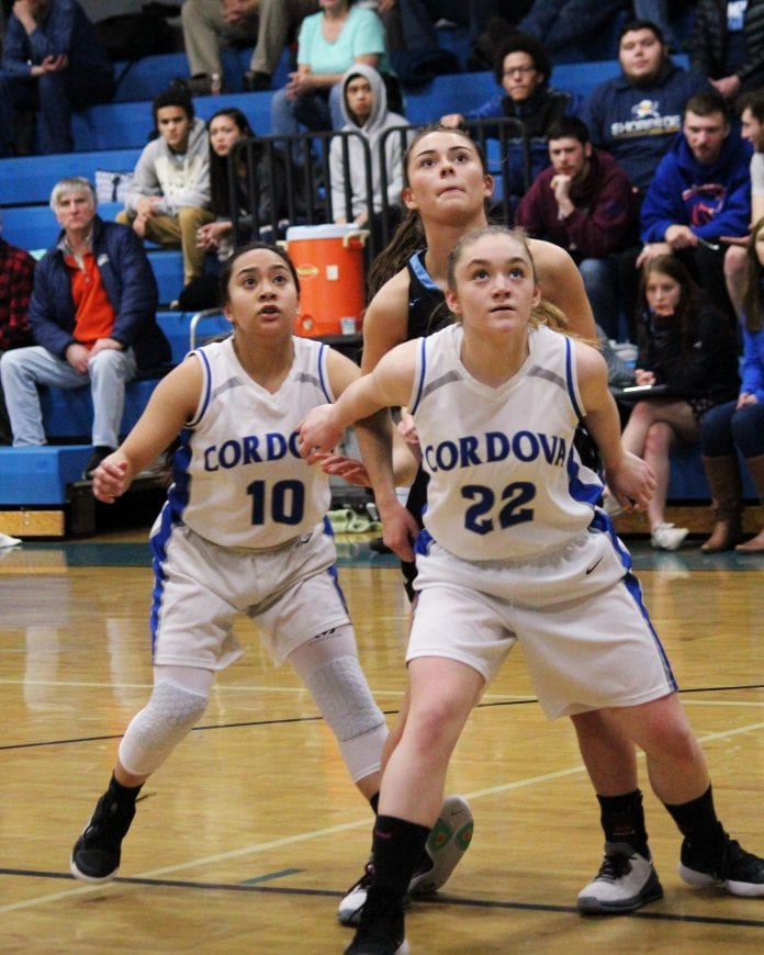 From left, Edrea Navarro and Inga Arvidson block out a taller Valdez player to secure a rebound for the Lady Wolverines. Photo by Mikie McHone/For The Cordova Times