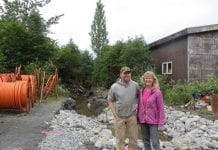 Andy and Laura Hanson stand in front of the engineered sediment basin on their Center Drive lot in July. Photo courtesy of Copper River Watershed Project