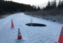 At Mile 19.5 traffic cones surrounds a large hole caused by a collapsed culvert. Perhaps a Christmas tree with a red light atop, rather than alder, should have been stuck in the ho-ho-hole. Photo by Dick Shellhorn/The Cordova Times