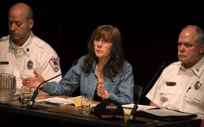 Emergency Coordinator Joanie Behrends, accompanied by Police Chief Mike Hicks, right, and Fire Marshall Paul Trumblee, left, talks to the public during an earthquake/tsunami debriefing held at the North Star Theatre on Tuesday, Jan. 30, 2018.