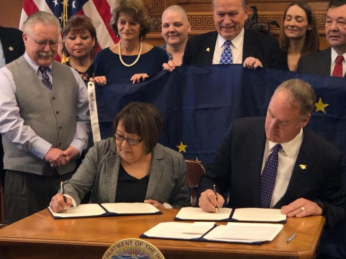 Della Trumble, spokeswoman for the King Cove Native Corp. signs documents with Interior Secretary Ryan Zinke to approve a link connecting King Cove and Cold Bay by road. Photo courtesy of the King Cove Native Corp.