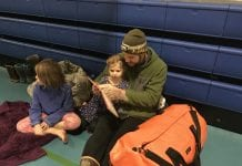 Kevin and Nora Haisman read to pass the time at the shelter, as Isla looks on. Check out their orange 'To Go' kit. Photo courtesy of Joanie Behrends