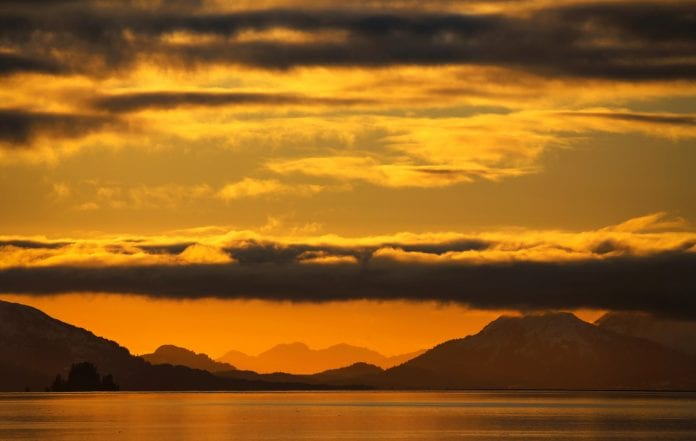 The sun sets down Orca Inlet as clouds roll in and over the mountains as seen from the harbor on Wednesday, Feb. 7, 2018. Photo by Emily Mesner/The Cordova Times