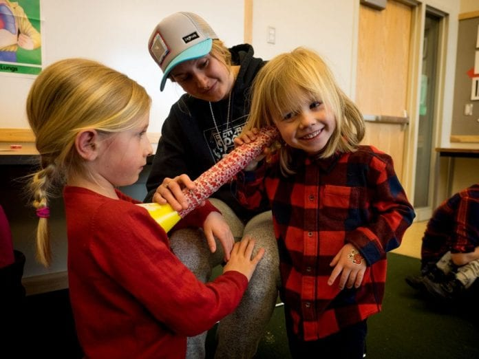 Sierra McAniff helps Kash Quinn listen to his sister, Kinley's, heartbeat with a homemade stethoscope. Photo by Teal Barmore/for Prince William Sound Science Center