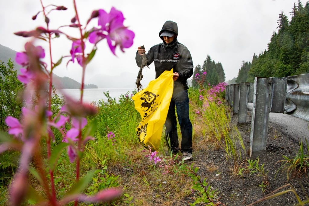 Volunteer Jonah Reutov cleans up garbage near the shore of Eyak Lake. The Saturday, July 27, 2019, cleanup organized by the Copper River Watershed Project and the Forest Service removed 12 cubic yards of waste from the area. Photo by Zachary Snowdon Smith/The Cordova Times