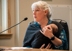 Kristy Andrew, accompanied by her child Ellie Andrew-Jaguey, testifies before the Alaska House Transportation Committee. Two hundred and fifty other residents crowded into the Cordova Center on Saturday, July 27, 2019, to testify on a proposed seven-month ferry stoppage. Photo by Zachary Snowdon Smith/The Cordova Times