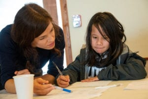 From left: Kathrin Kaiser helps Brooklyn Curry write a story in the Eyak language. This exercise was part of Eyak Culture Camp activities on Sunday, Aug. 4, 2019. Photo by Zachary Snowdon Smith/The Cordova Times