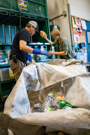 From left: David Saiget and Shae Bowman load plastic bottles into the AC Value Center baling machine. The Copper River Watershed Project compacted a bale of plastic bottles for recycling on Aug. 7, 2019. Photo by Zachary Snowdon Smith/The Cordova Times