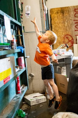 Drake Westing, 4, pitches a bottle into the AC Value Center baling machine. The Copper River Watershed Project compacted a bale of plastic bottles for recycling on Aug. 7, 2019. Photo by Zachary Snowdon Smith/The Cordova Times
