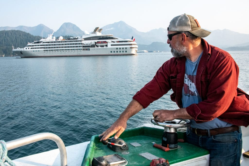 Bret Bradford, piloting the F/V Nerka, watches the cruise ship Le Soléal depart. The ship first visited Cordova on Aug. 21. Photo by Zachary Snowdon Smith/The Cordova Times