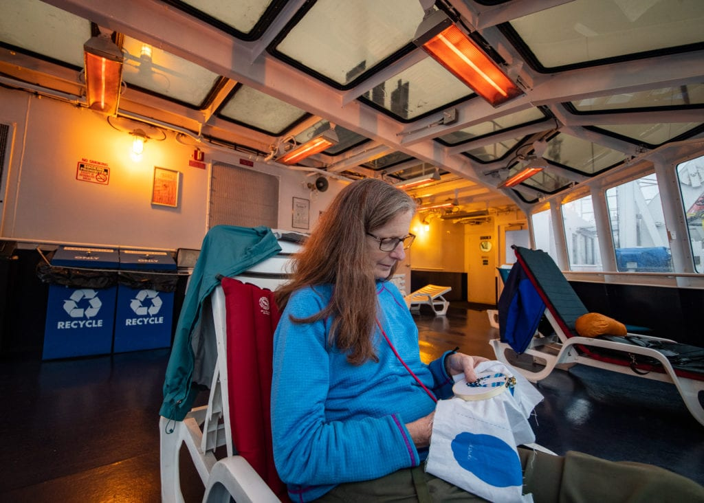 Resident Torie Baker practices embroidery during a voyage from Valdez to Cordova. (Sept. 19, 2019) Photo by Zachary Snowdon Smith/The Cordova Times