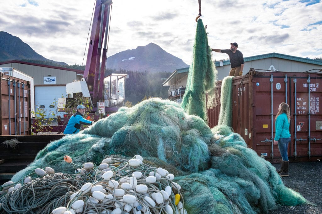 From left: Matt Doucett, Gerald McCune and Shae Bowman load loose fishing nets into a shipping container for recycling. (Oct. 3, 2019) Photo by Zachary Snowdon Smith/The Cordova Times