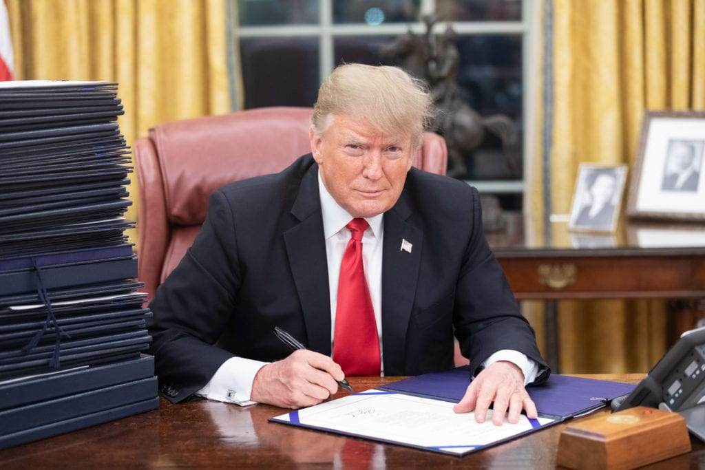President Donald J. Trump in the Oval Office with a stack of documents awaiting his signature. Photo courtesy of Shealah Craighead/The White House