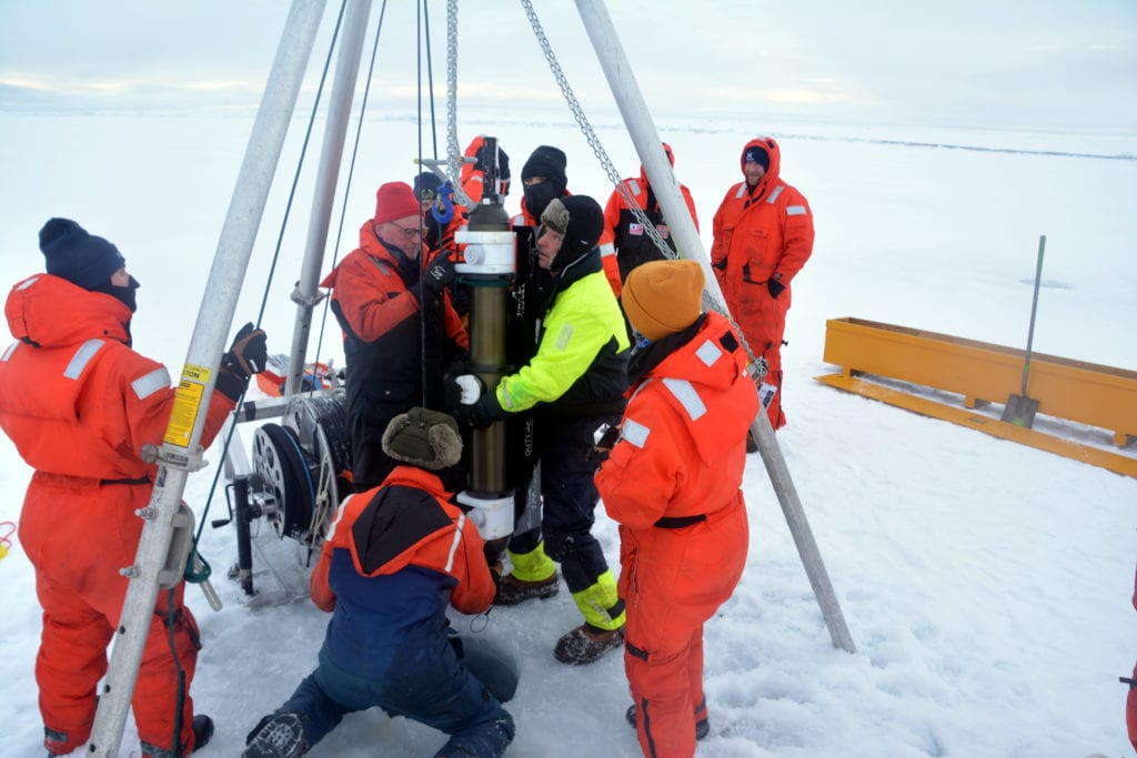 Coast Guard Cutter Healy crewmember Ens. Cody Williamson, left, oversees deployment of an ice profiler by John Kemp and James Dunn of Woods Hole Oceanographic Institute while on an ice floe in the Arctic Ocean on Sept. 19. The crew and scientists deployed numerous scientific sensors during the ice station to gather data for Arctic research. Photo courtesy of Ens. Trevor Layman