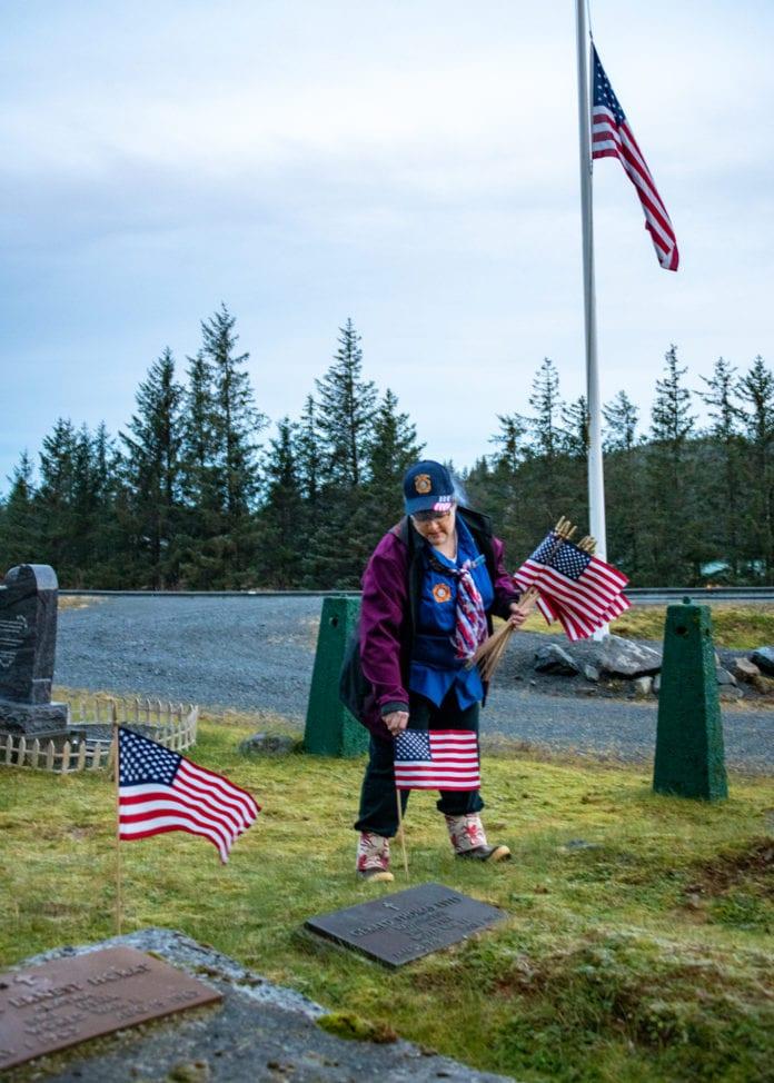 Wendy Ranney plants flags at Cordova Cemetery on Veterans Day. (Nov. 11, 2019) Photo by Zachary Snowdon Smith/The Cordova Times