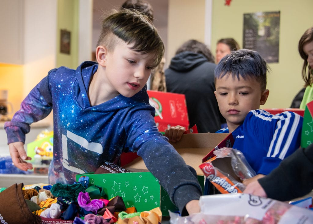 From left, Steven and Jaxon Pallas prepare care packages as part of the Operation Christmas Child program. (Nov. 9, 2019) Photo by Zachary Snowdon Smith/The Cordova Times