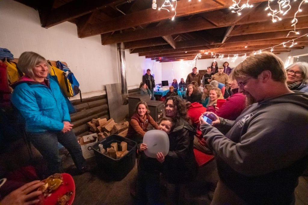 Outgoing Copper River Watershed Project Executive Director Kristin Carpenter (left) listens to a tribute read by Native Village of Eyak fish biologist Matt Piche (right). (Nov. 11, 2019) Photo by Zachary Snowdon Smith/The Cordova Times
